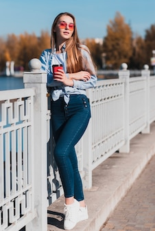 Blondine, die mode nahe bei einem geländer aufwerfen