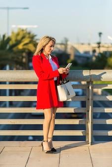Blondine, die rote jacke unter verwendung eines telefons steht auf der straße tragen