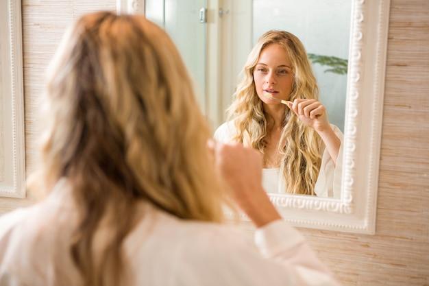 Blondine, die zu hause ihre zähne im badezimmer putzen
