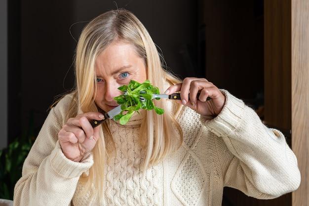 Blondine frau mittleren alters, die salat in der küche, gesundes nahrungsmittelkonzept isst