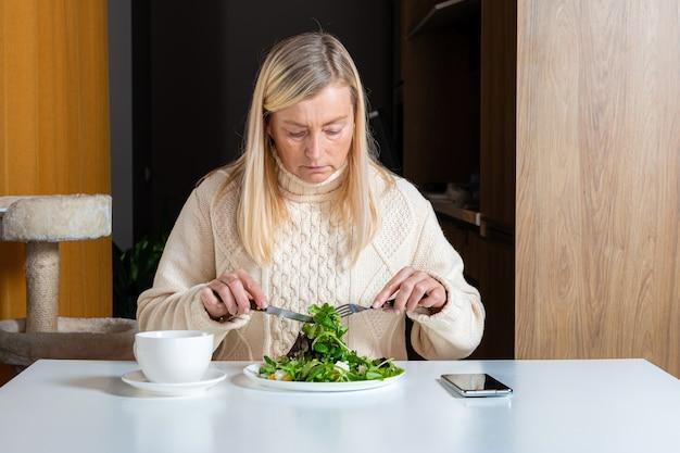 Blondine frau mittleren alters, die salat isst und tee in der küche, gesundes nahrungsmittelkonzept trinkt