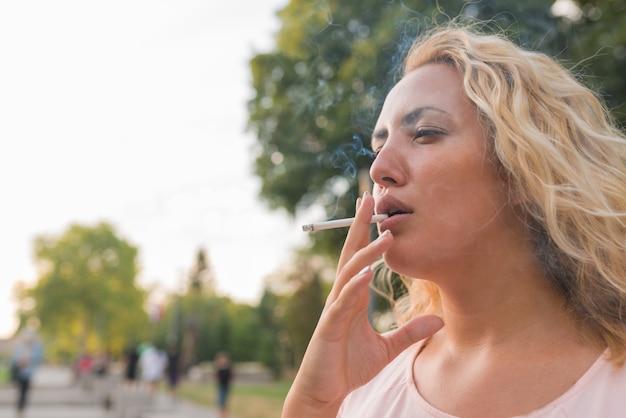 Blondine genießt eine zigarette