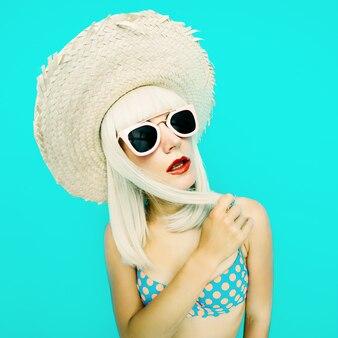 Blondine im badeanzug polka dot auf blauem grund. retro-sommer-stil