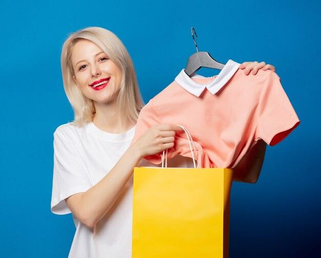 Blondine im weißen t-shirt mit einkaufstasche und kleid auf kleiderbügel auf blauem raum