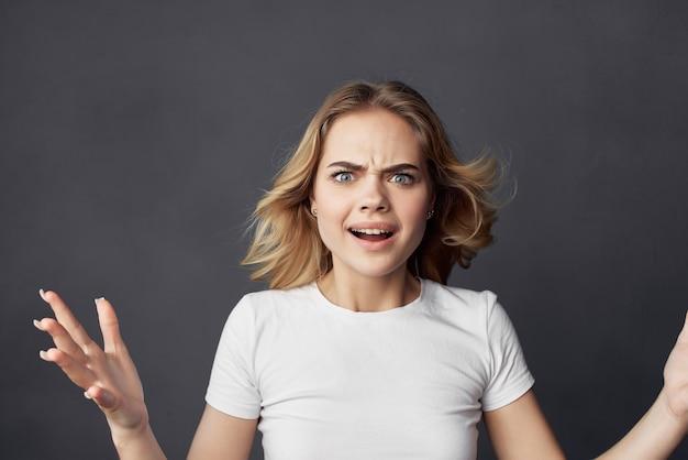 Blondine im weißen t-shirt modell posiert studio dunklen hintergrund
