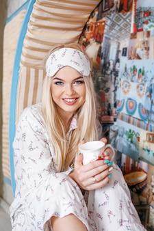 Blondine in den pyjamas kaffee morgens trinkend. schlafmaske.
