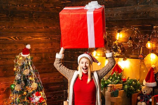 Blondine in der weihnachtsmütze und in den geschenken, die weihnachtsferien feiern, die große kiste haben