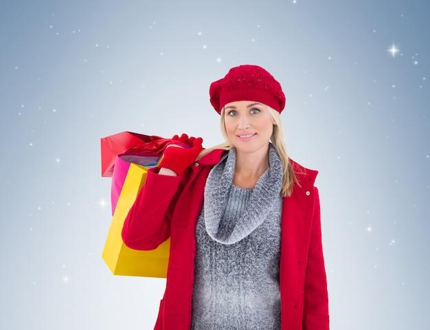 Blondine in der winterkleidung, die einkaufstaschen hält