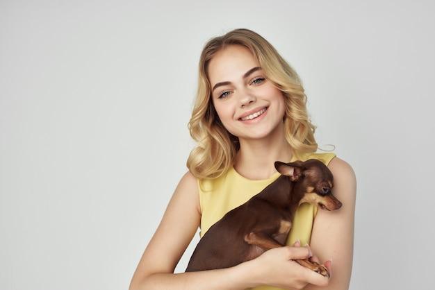 Blondine in einem gelben kleid macht spaß mit der mode eines kleinen hundes