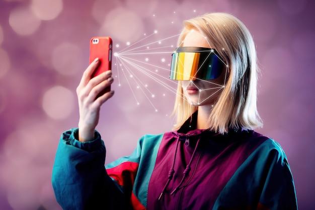 Blondine in vr-brille hält handy mit gesichts-scan-algorithmus