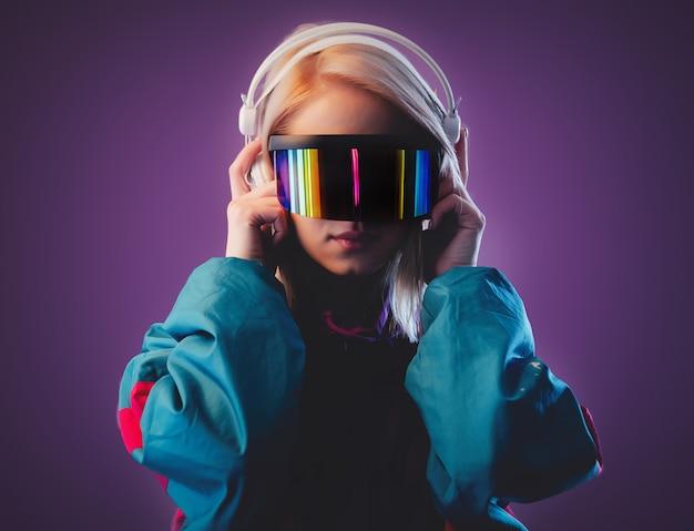 Blondine in vr-brille und kopfhörer an rosa wand