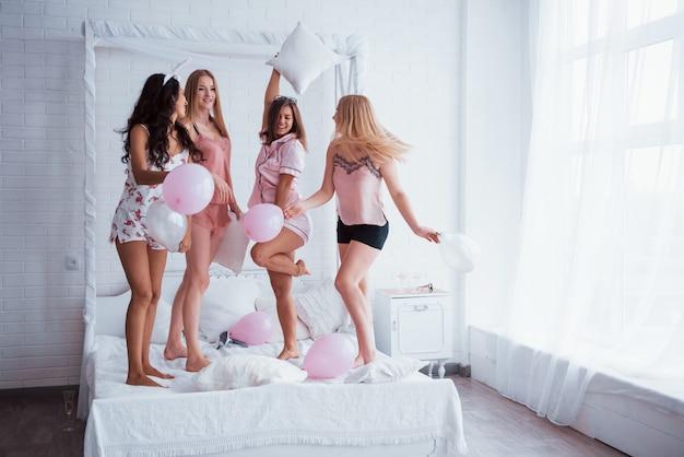 Blondine mit brille tanzt und hat spaß. stehen auf dem luxus weiß schlecht in der ferienzeit mit luftballons und hasenohren. vier schöne mädchen in nachtwäsche feiern