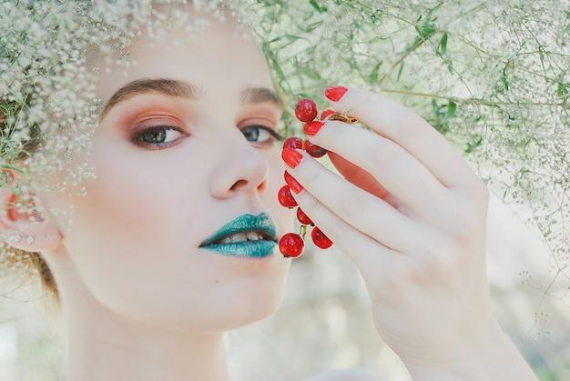 Blondine mit den grünen lippen, die rote johannisbeerbündel halten. konzept der mutter natur