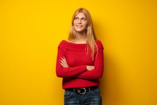 Blondine über der gelben wand, die oben beim lächeln schaut