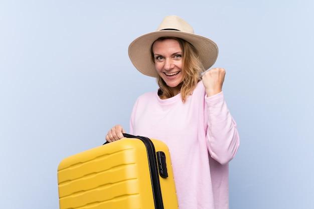 Blondine über lokalisierter wand in den ferien mit reisekoffer und einem hut