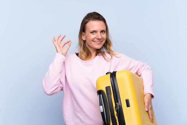 Blondine über lokalisierter wand in den ferien mit reisekoffer und herstellung des okayzeichens