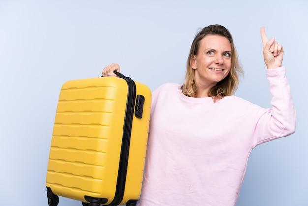 Blondine über lokalisierter wand in den ferien mit reisekoffer und oben zeigen