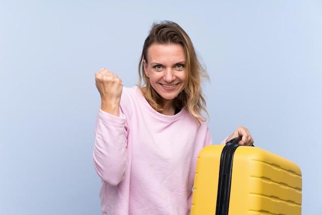 Blondine über lokalisierter wand in den ferien mit reisekoffer