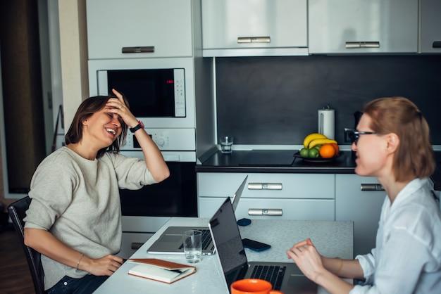 Blondine und brünette mit laptops im küchenbereich. zwei süße frauen arbeiten, sitzen am tisch und stehen sich in einer entspannten wohnumgebung gegenüber.