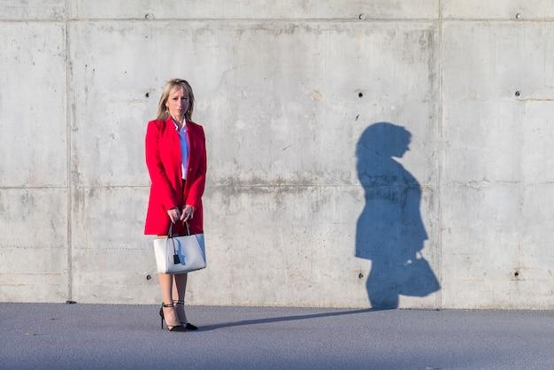 Blondine, welche die rote jacke und schwarzes hemd stehen in der stadt tragen