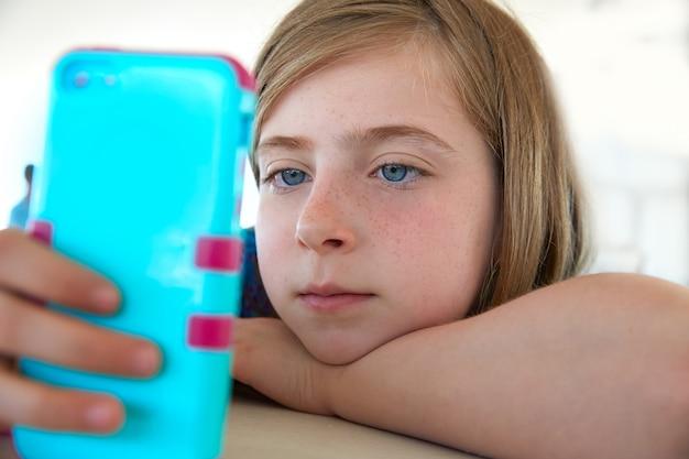 Blonk-kindermädchen, das smartphone schaut