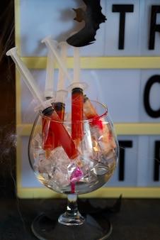 Bloody mary-cocktail in der spritze mit netz für halloween-parteifeier.