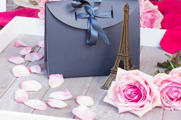 Bloomin rosa rosen mit gifl-tasche, die auf holztisch liegt