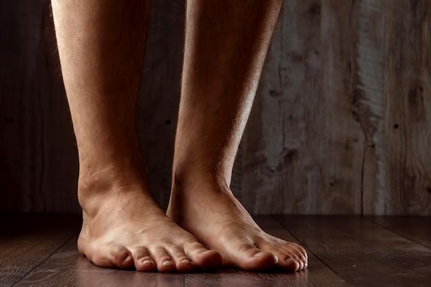Bloße füße auf hölzernem hintergrund