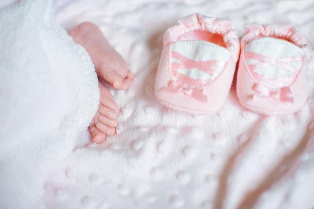 Bloße füße eines niedlichen neugeborenen babys in der warmen weißen decke
