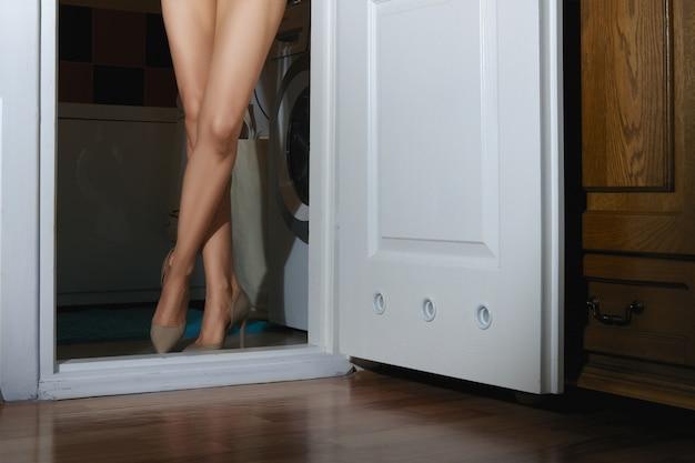 Bloße weibliche beine in der tür des badezimmers