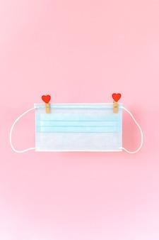 Blu schützende gesichtsmaske, die an wäscheklammern mit herzen am seil hängt.