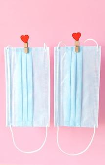 Blu schützende gesichtsmasken fliegen auf wäscheklammern mit herzen am seil.