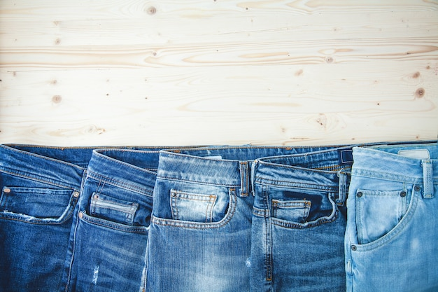 Blue jeans auf einem hölzernen hintergrund kopien-raum-draufsichtplatz für text