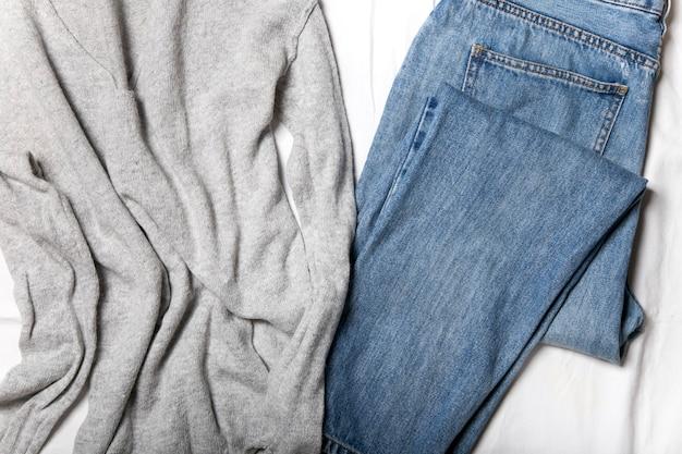 Blue jeans ein strickpullover auf einem weißen laken draufsicht auf ein lässiges damen tagesoutfit