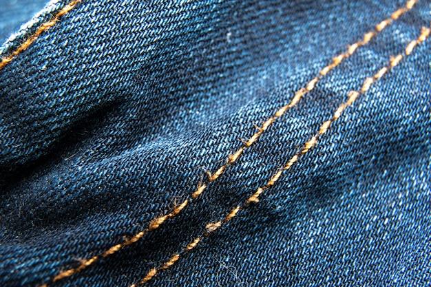 Blue jeans-gewebemakronaht-musterhintergrund / denimjeansbeschaffenheit / blue jeans-beschaffenheit für irgendeinen hintergrund.