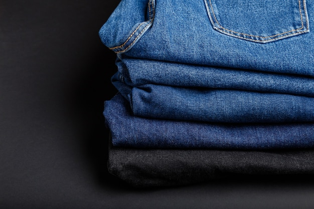 Blue jeans hosenstapel. stapel blue jeans auf schwarzem hintergrund mit kopienraum.