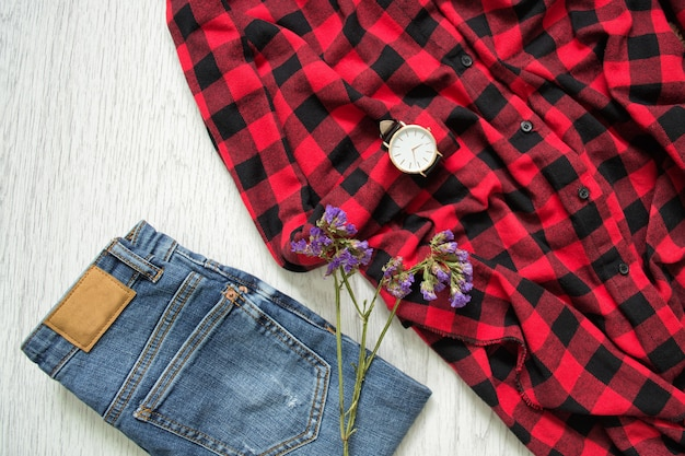 Blue jeans, kariertes hemd, uhren und blume. holzuntergrund. modisches konzept