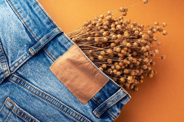 Blue jeans mit braunem lederetikett und trockenem leinen, nahaufnahme. jeans-textur. mode-denim-hintergrund zum nähen, kopienraum. etikett auf der kleidung zur angabe von größe und firma.
