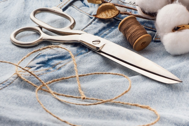 Blue jeans, schere, metallspulen mit fadennahaufnahme. schneiderei des lässigen denim-bekleidungskonzepts. schneiden und nähen, hintergrund. natürliche jeansstoffe.