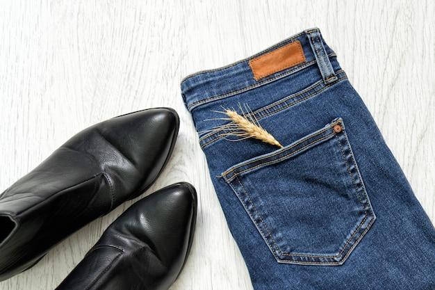 Blue jeans, schwarze schuhe und weizenähre