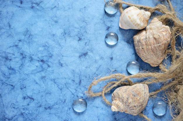 Blue sea flat lag mit muscheln und einem seil