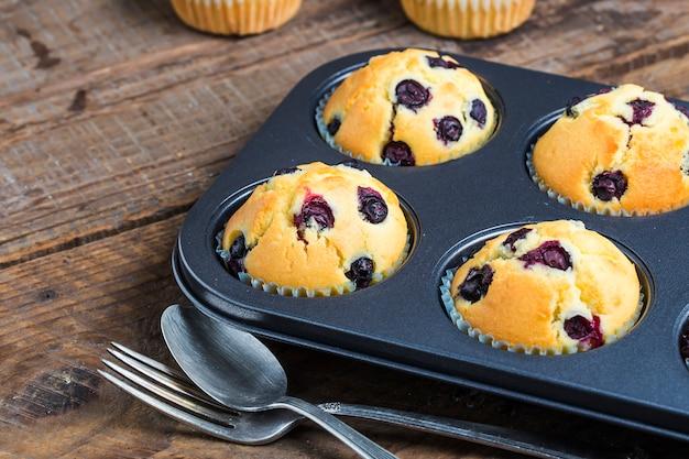 Blueberry muffins mit puderzucker und frischen beeren