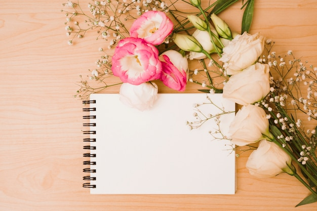 Blühen sie blumenstrauß mit leerem gewundenem notizblock auf hölzernem hintergrund