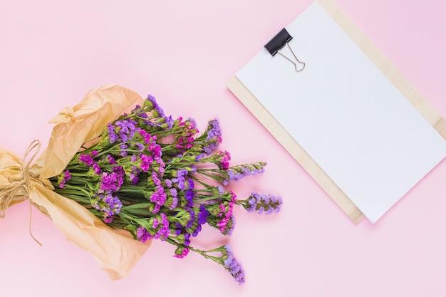 Blühen sie den blumenstrauß, der im braunen papier nahe dem weißen leeren papier auf klemmbrett eingewickelt wird