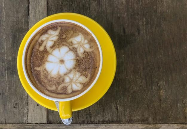 Blühen sie formoberfläche der heißen kaffeetasse auf hölzernem tabellenhintergrund.