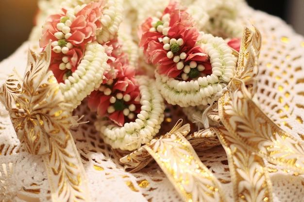 Blühen sie girlanden auf einem goldbehälter am thailändischen hochzeitszeremonientag der tradition. jasmin-girlande