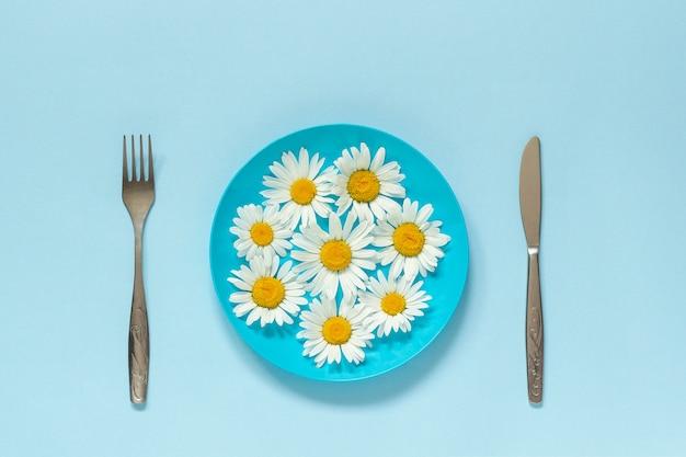 Blühen sie kamille gänseblümchen auf blauem teller und besteck konzeptvegetarismus, gesunde ernährung oder diät