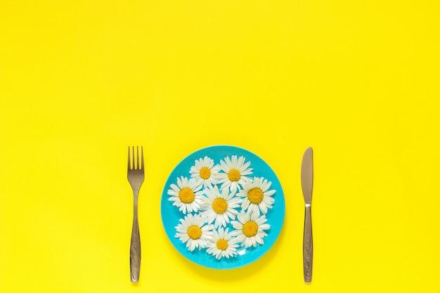 Blühen sie kamille gänseblümchen auf blauer platte, gabelmesser auf gelbem konzeptvegetarismus, diät der gesunden ernährung