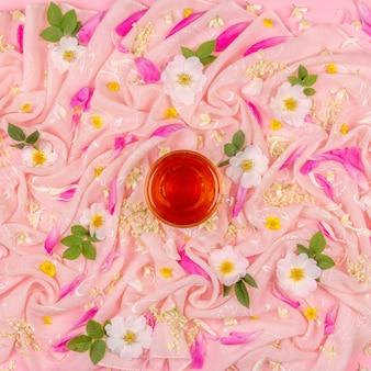 Blühen sie zusammensetzung von weißen und rosa blumen und und eine tasse tee auf rosa stoff