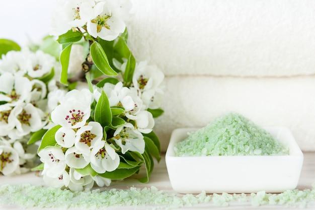 Blühende apfelbaumblumen, aromatisches meersalz und handtücher. konzept für wellness-, beauty- und gesundheitssalons.